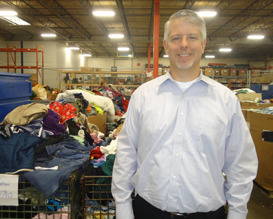 Dan Buron standing in a warehouse with donated clothing behind him