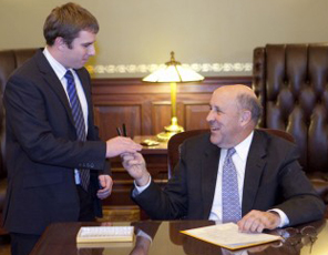 Governor Jim Doyle hands a pen to Steven Kulig