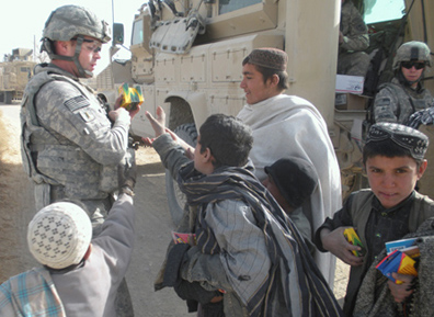 Soldier Brian Bell hands out crayons and other school supplies to a group of children.