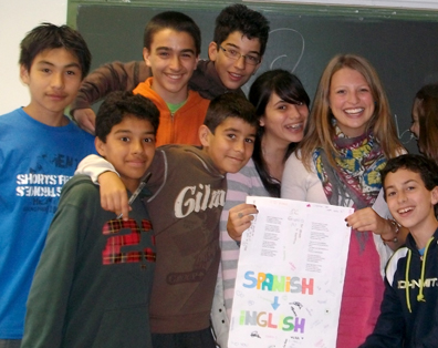 woman with seven students holding sign with an arrow pointing from the word Spanish to the word English