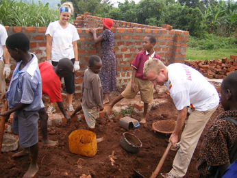 adults and children at school building site
