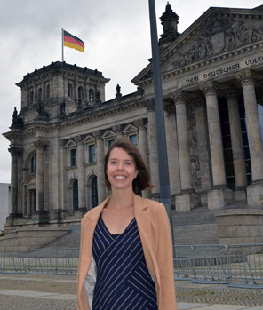 Woman standing in front of building flying German flag