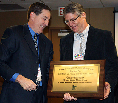 Man handing a plaque to another man