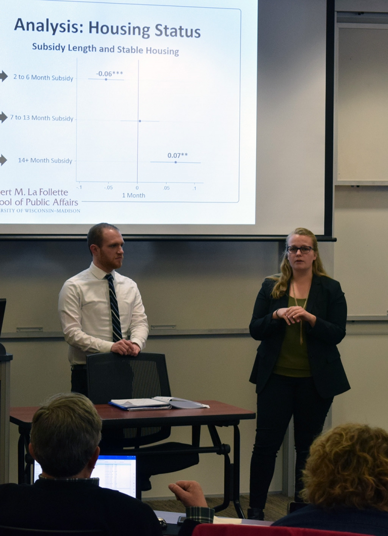 During practice sessions for presenting their Workshop project reports, Anna Brunner (MPA '17) responds to a question, while Daniel Benson (MPA '17) looks on.